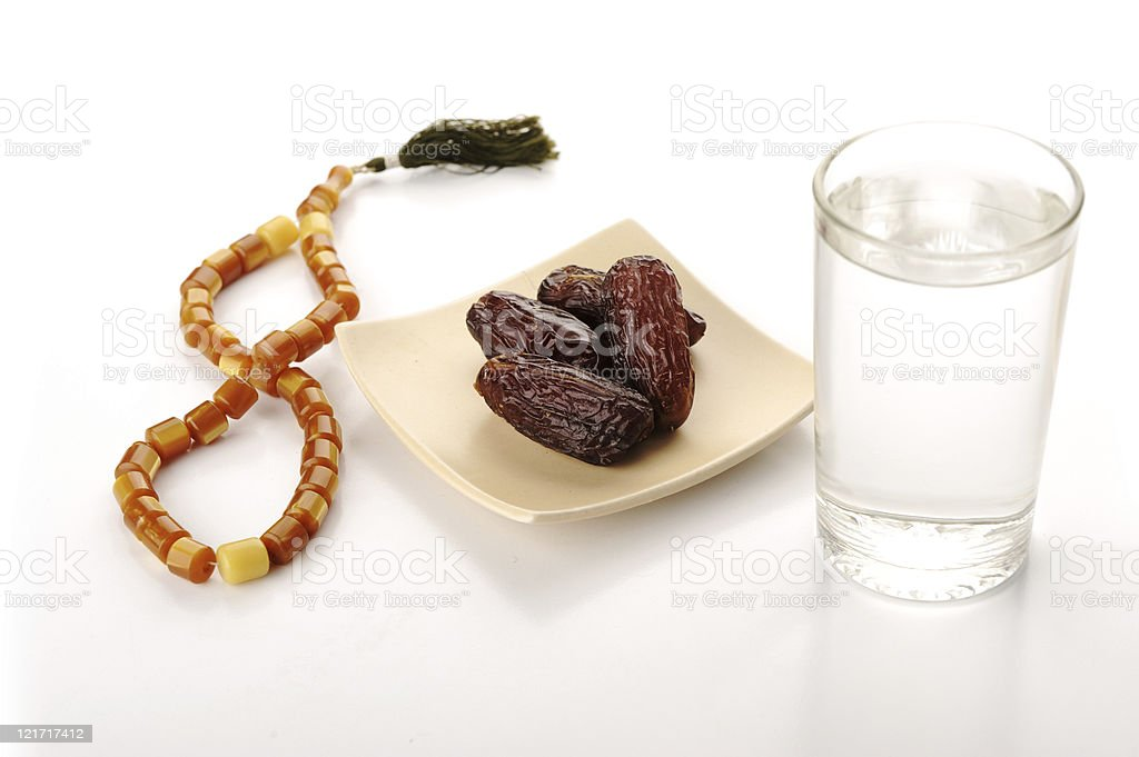 Dates, water and rosary beads for Ramadan stock photo