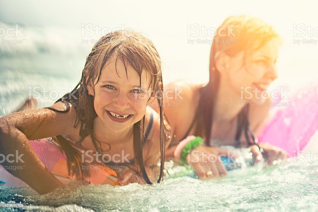 Daughter and mother having fun in sea stock photo