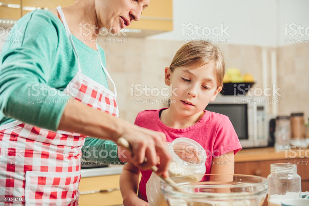 Daughter and mother making  pizza dough stock photo