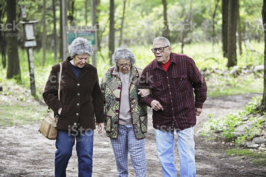 Daughter And Senior Parents Walking Together on Nature Trail royalty-free stock photo