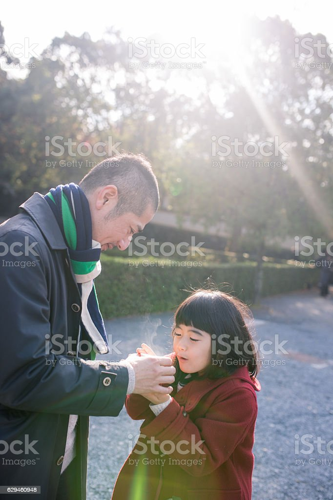 Daughter blowing on hot tea with father in the morning stock photo