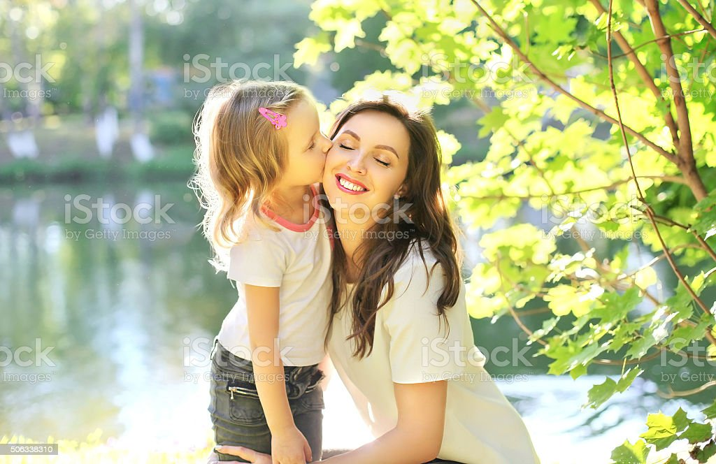 Daughter child kissing happy mother in summer day stock photo