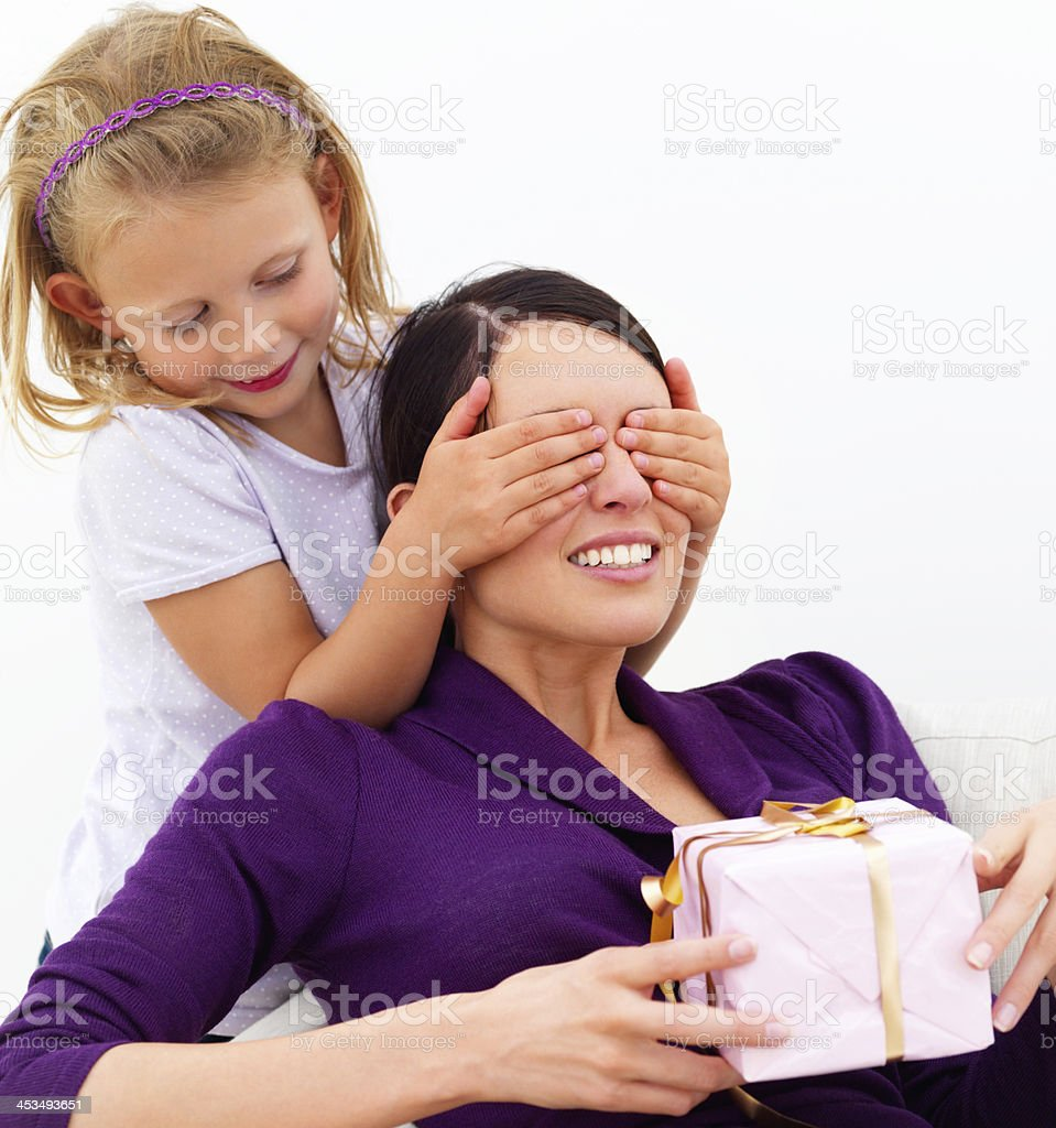 Daughter closing eyes of mother holding gift on white royalty-free stock photo