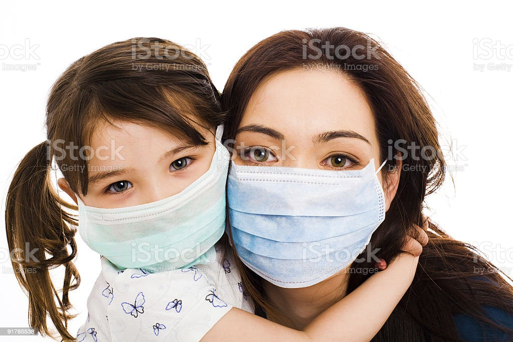 Daughter embracing mother as they both wear hospital masks stock photo