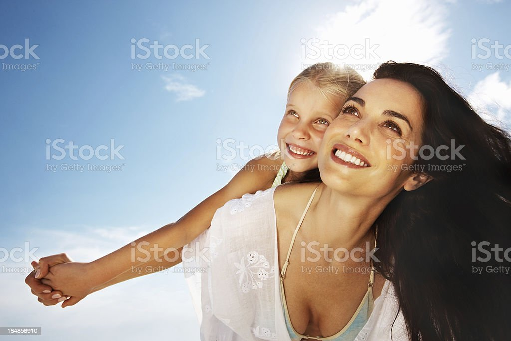 Daughter enjoying a piggy back ride on mother royalty-free stock photo