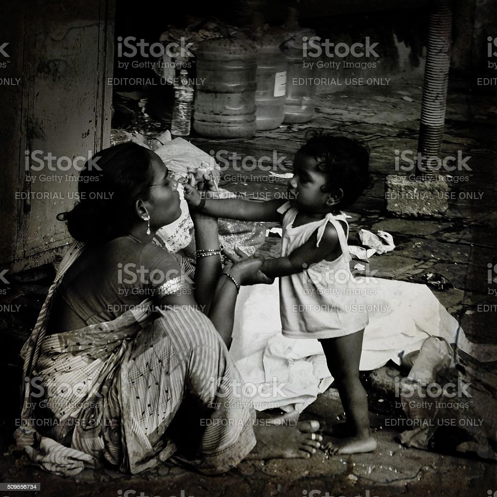 Daughter giving food to her mother on street-homeless stock photo
