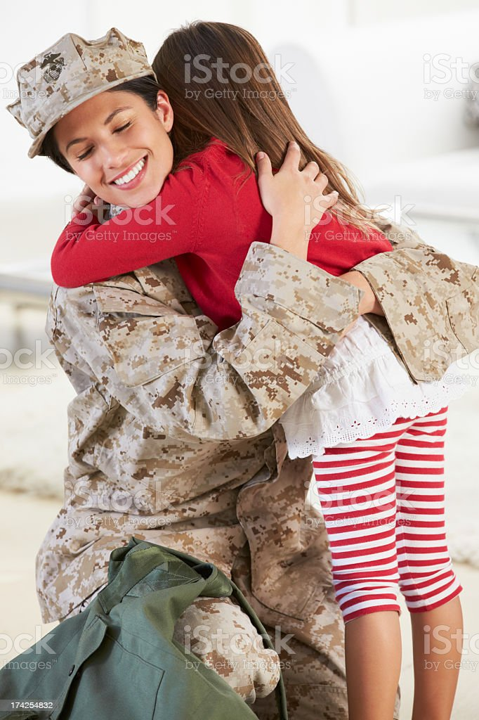 Daughter giving her military mother a hug, mother in fatigue stock photo
