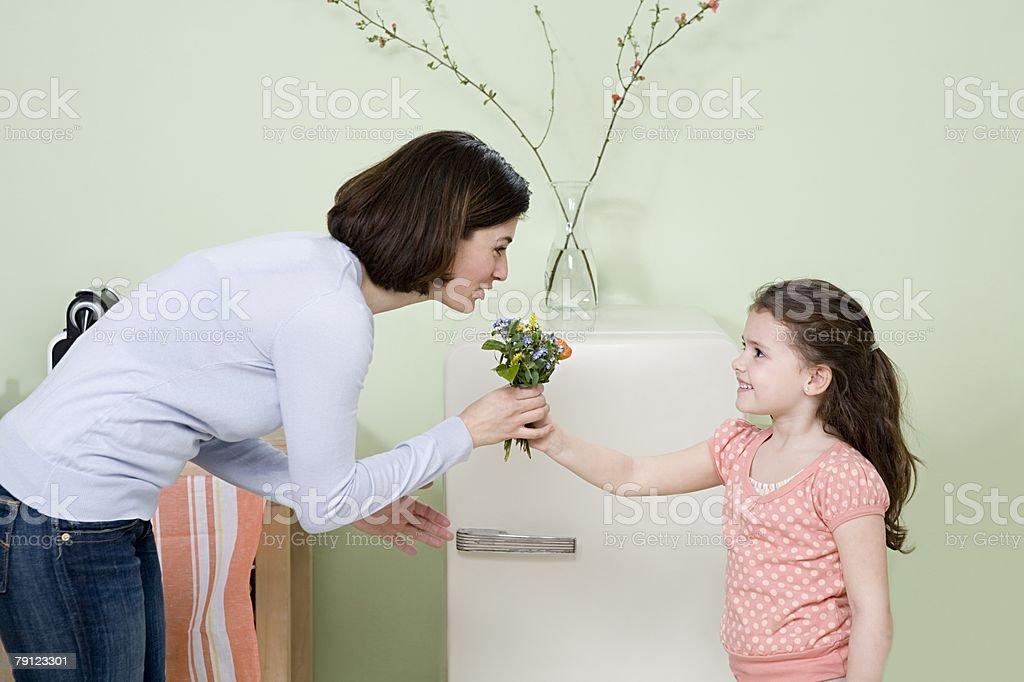 Daughter giving her mother flowers stock photo