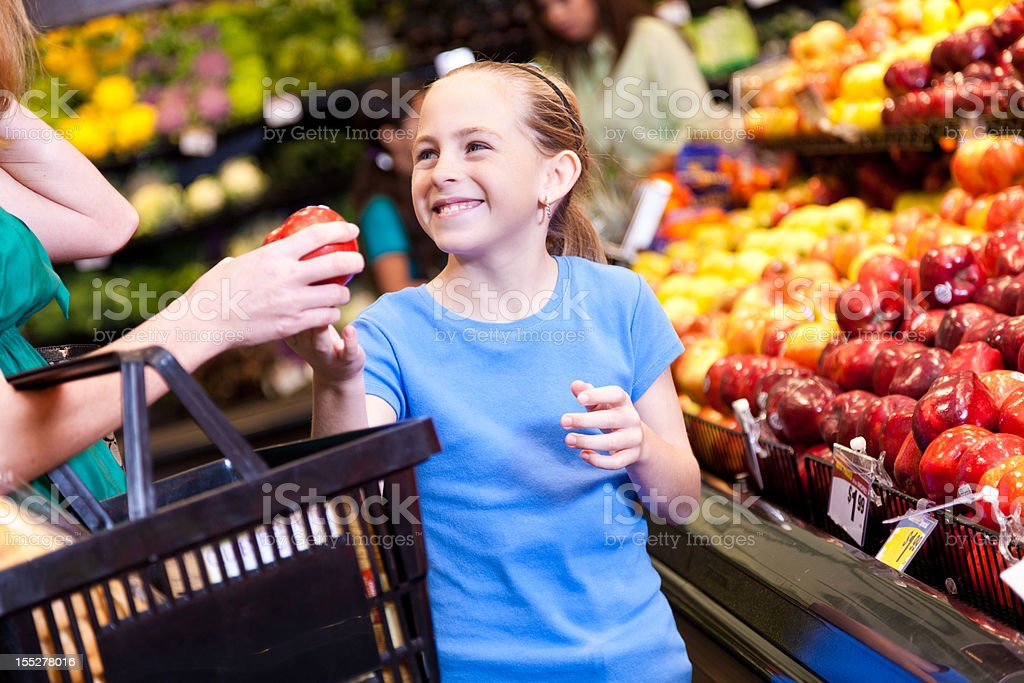 Daughter handing apple to mother at grocery store royalty-free stock photo