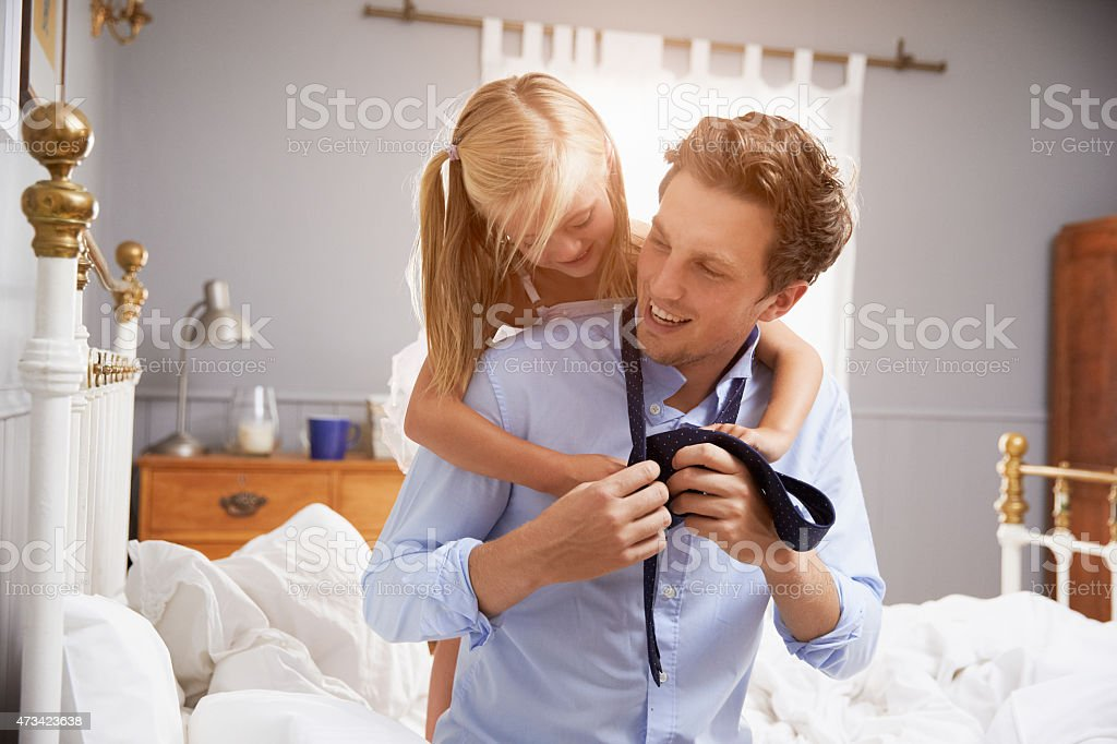 Daughter Helping Father To Get Dressed For Work stock photo