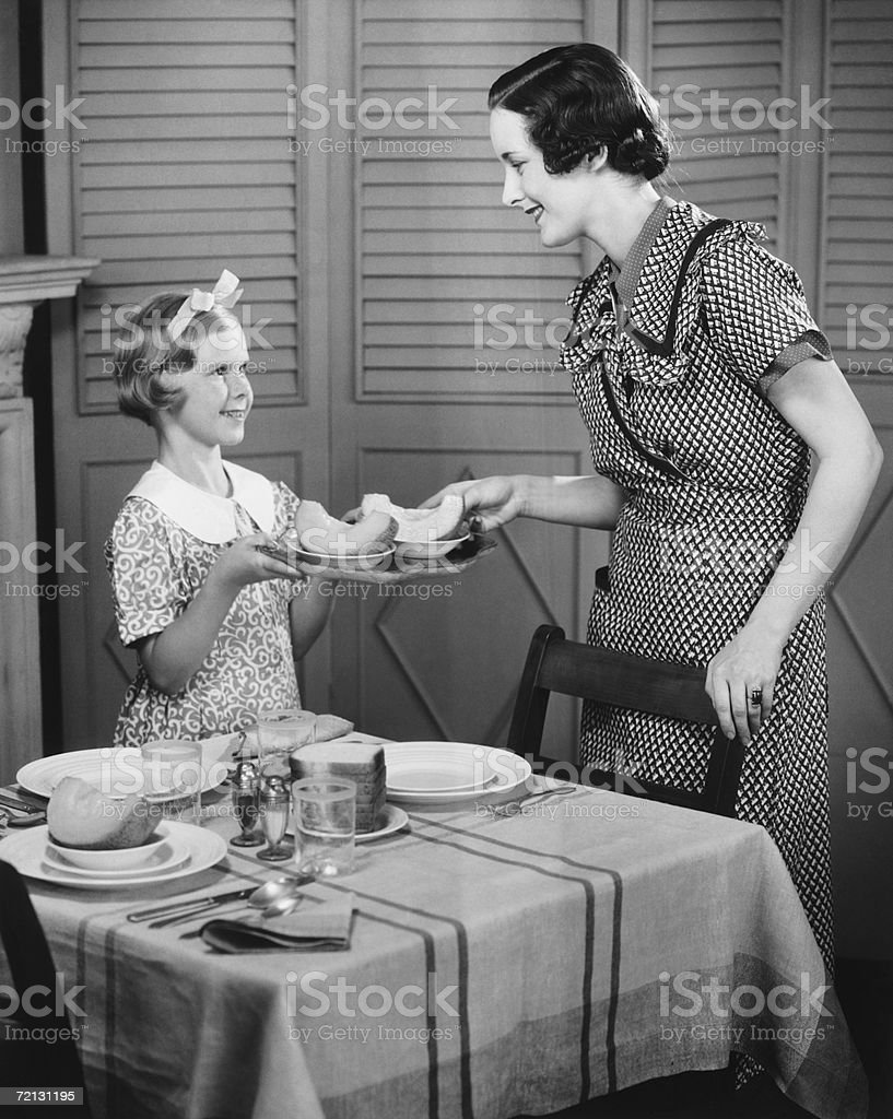 Daughter (8-9) helping mother setting table for breakfast (B&W) stock photo