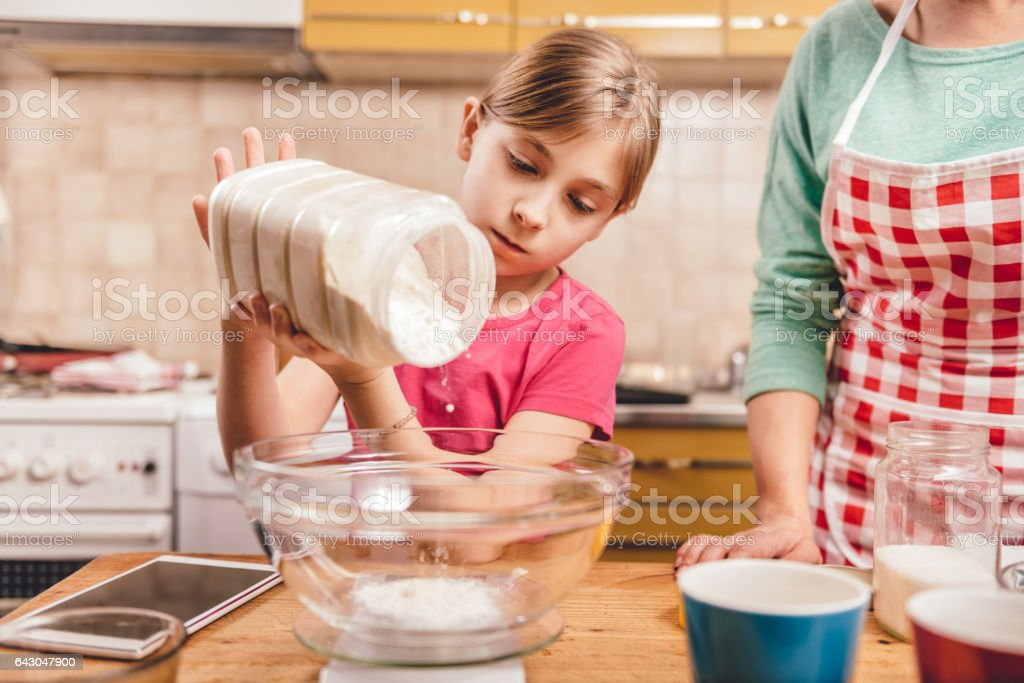 Daughter helping mother to making  pizza dough stock photo