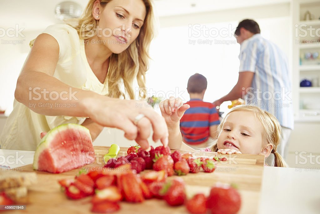 Daughter Helping Mother To Prepare Family Breakfast stock photo