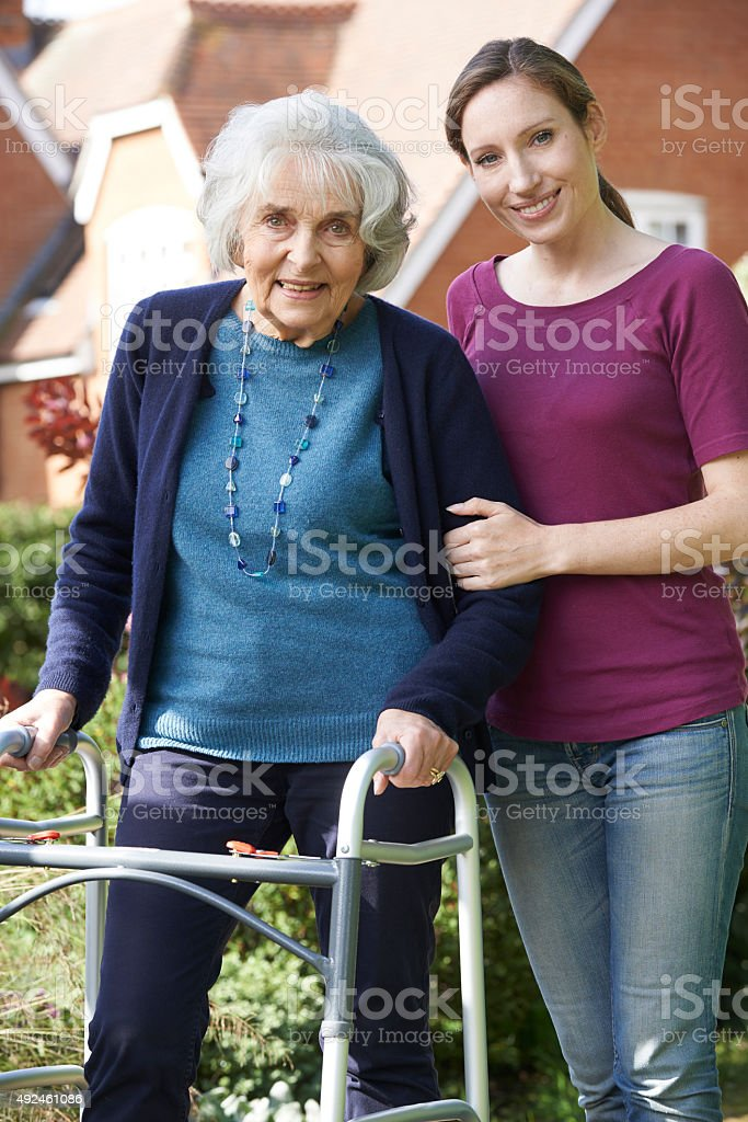 Daughter Helping Senior Mother To Use Walking Frame stock photo