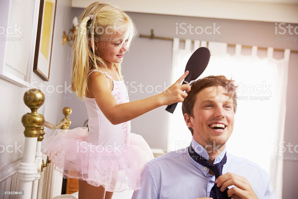 Daughter Helps Father To Get Ready For Work, Brushing Hair stock photo