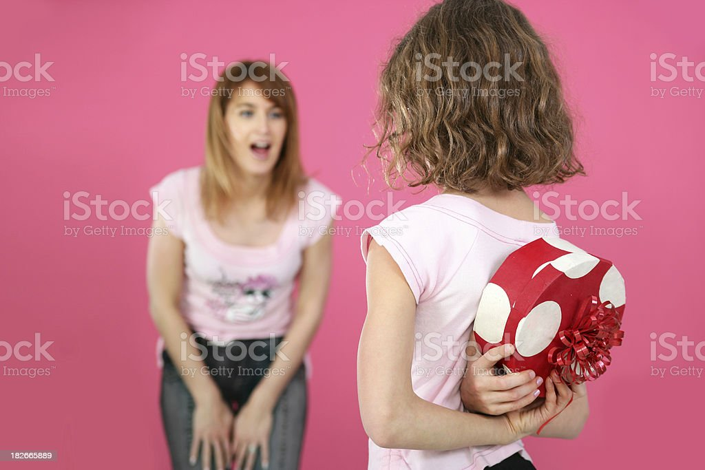 Daughter hiding a gift royalty-free stock photo