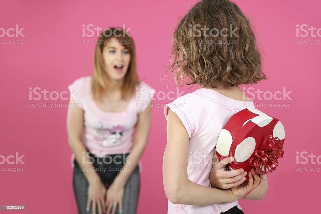 Daughter hiding a gift stock photo