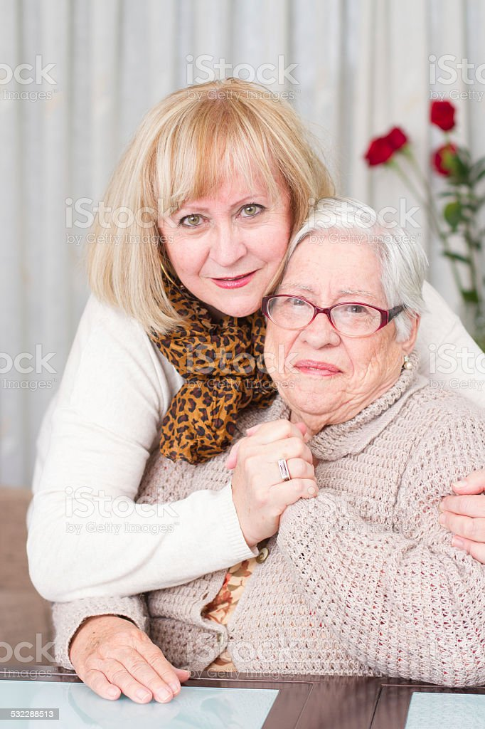 Daughter hugging her mother stock photo