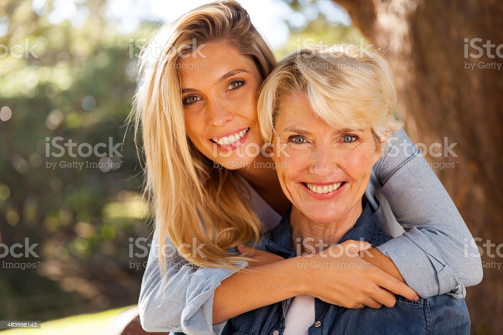 daughter hugging middle aged mother stock photo