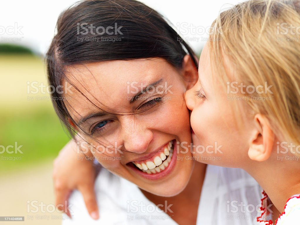 Daughter kissing her happy mother royalty-free stock photo