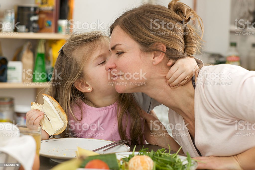 Daughter kissing mother on her cheek while eating royalty-free stock photo