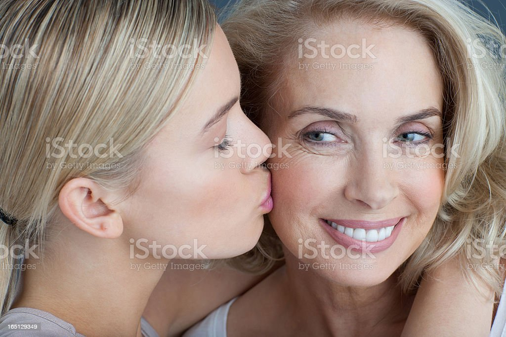 Daughter kissing smiling mother stock photo