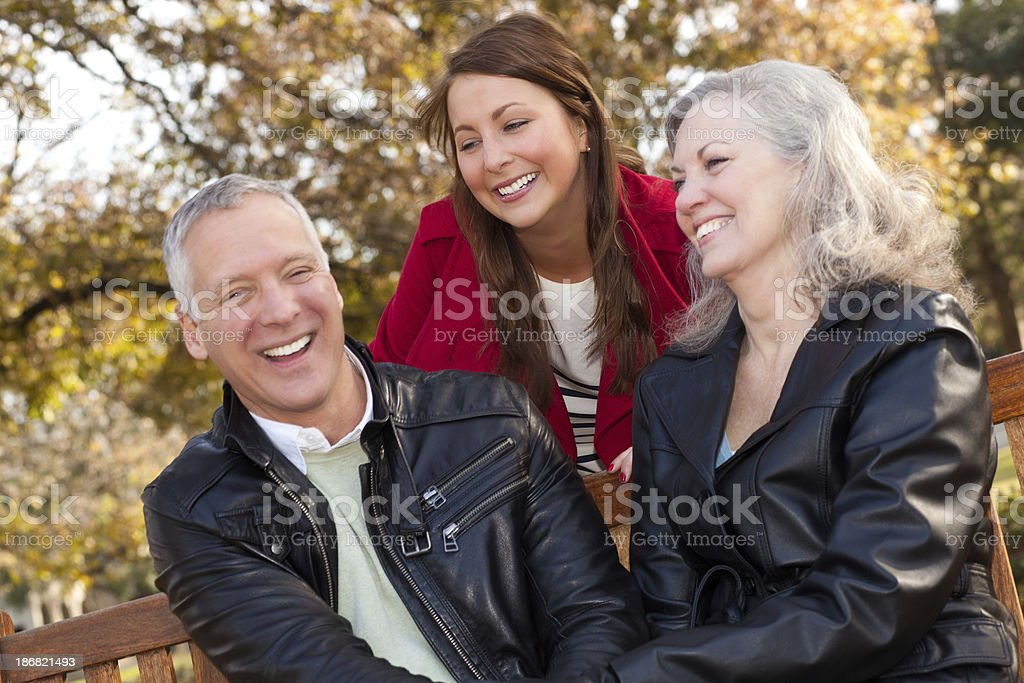 Daughter Laughing With Her Parents at a Park royalty-free stock photo
