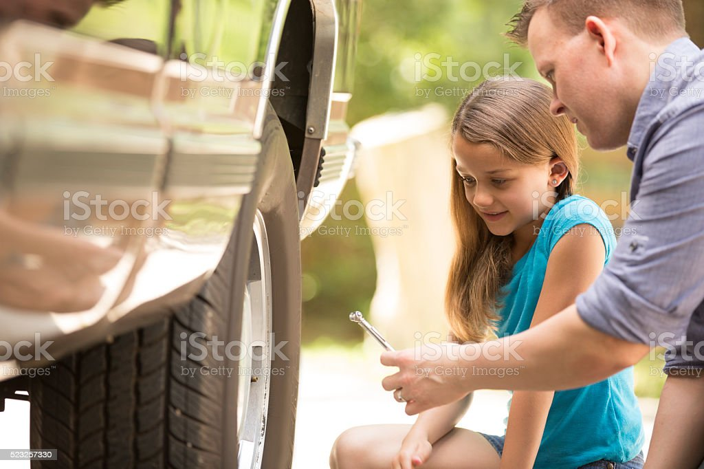 Daughter learning from father. Dad, child with tools, repairing vehicle. stock photo