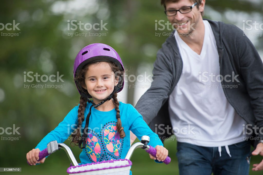 Daughter Learning How to Ride a Bike From Her Dad stock photo
