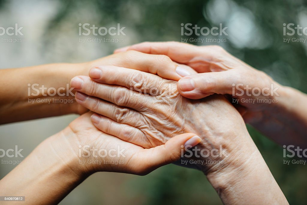 Daughter loving her senior mother and supporting her in living stock photo