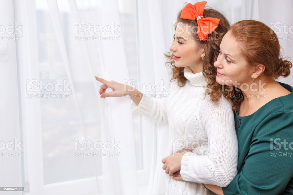 Daughter of the window shows the mother stock photo