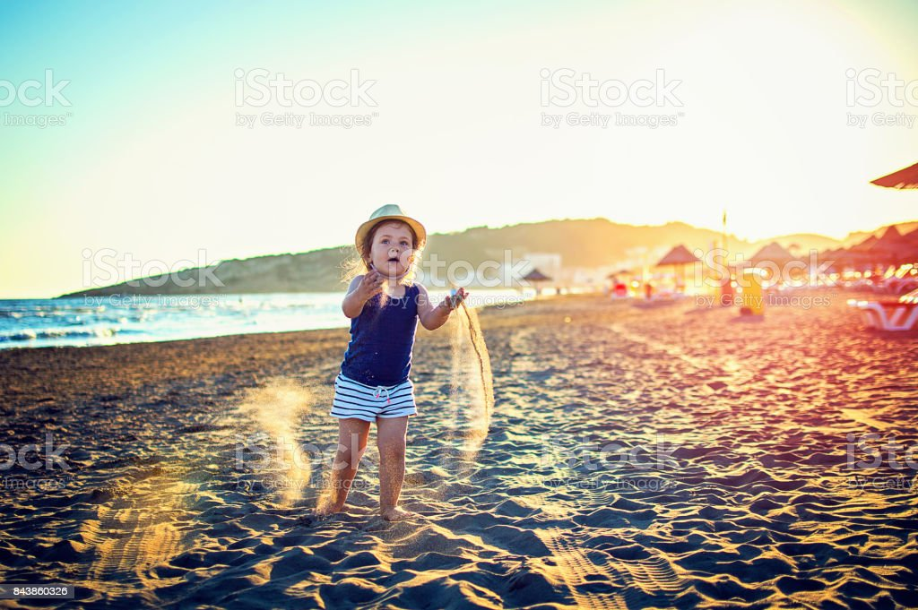 daughter on the beach, girl with little hat stock photo