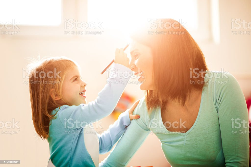 Daughter painting face to her mother stock photo