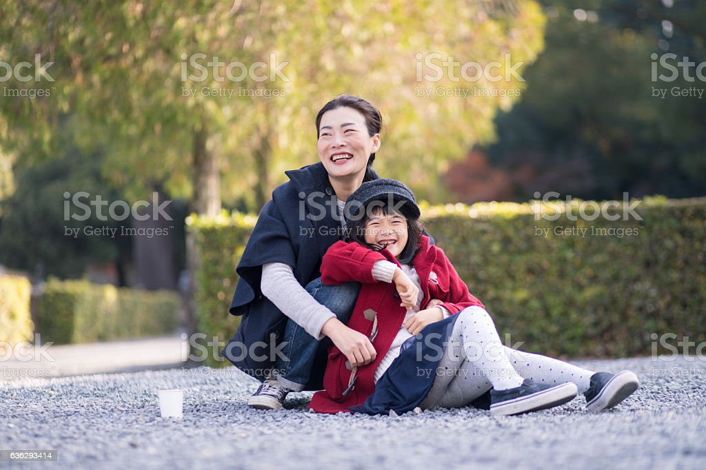 Daughter playing with mother in temple in the morning stock photo