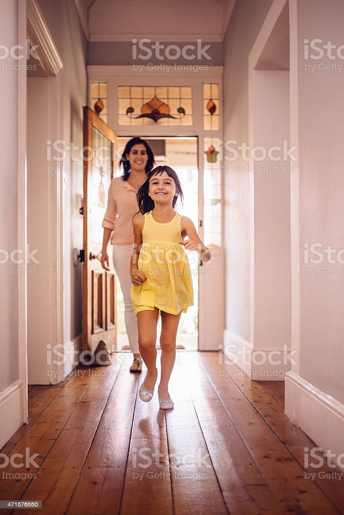 Daughter running ahead of her mom into their new home stock photo