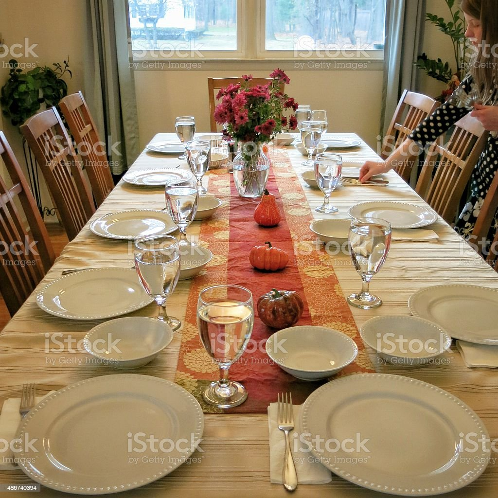 Daughter Setting the Thanksgiving Day Feast Table stock photo