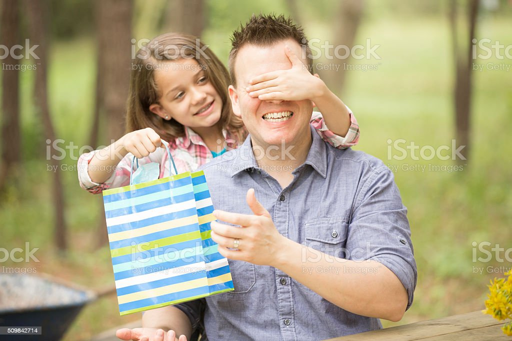Daughter surprises dad with Father's Day gift. Outdoors. Child, parent. stock photo