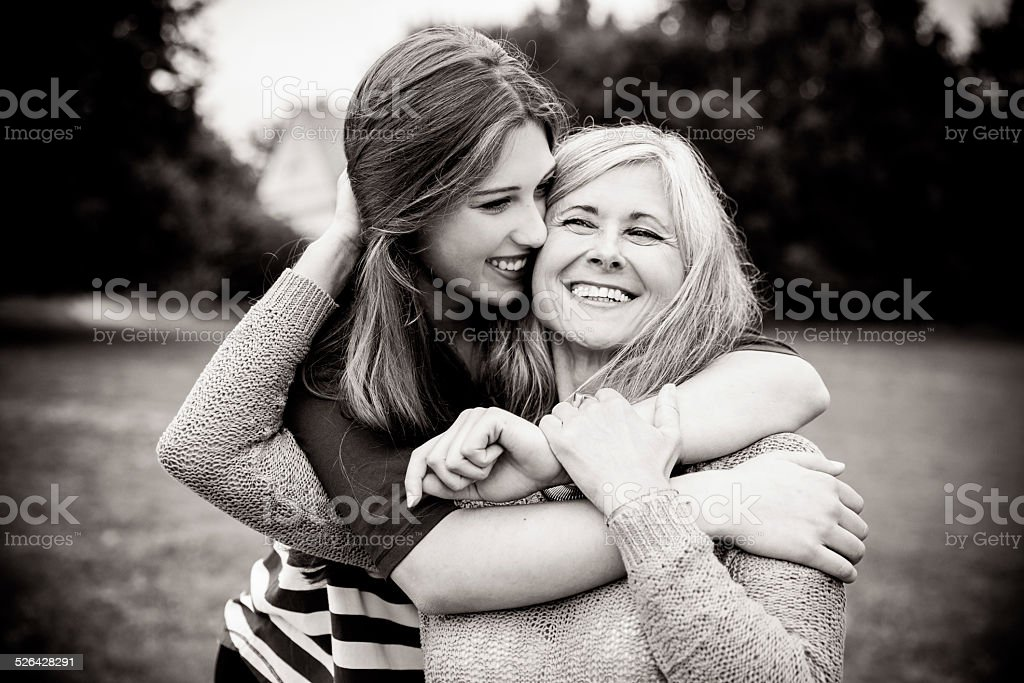 Daughter Surprises Mother With a Hug From Behind stock photo