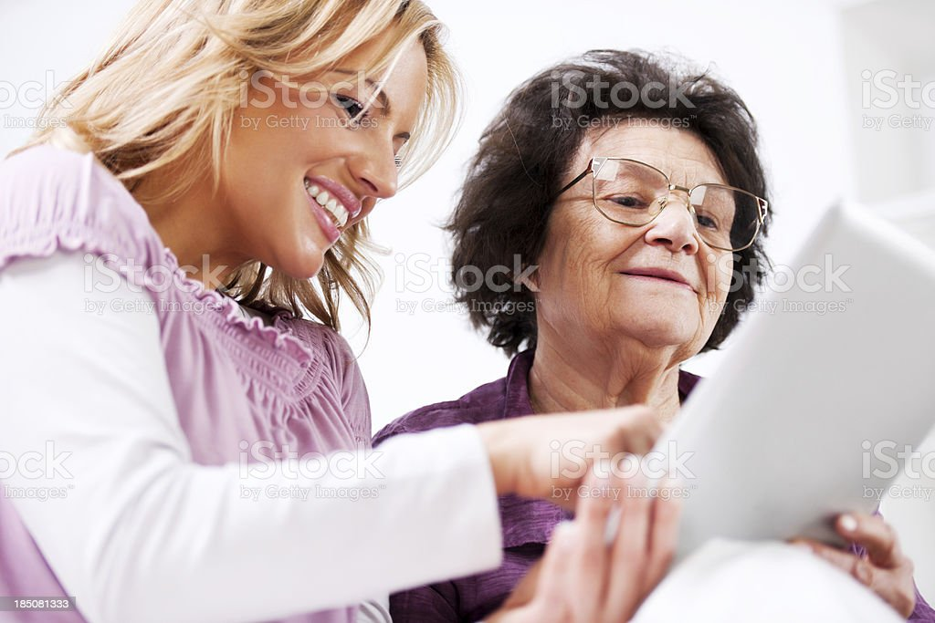 Daughter teaching her senior mother to use touchpad royalty-free stock photo