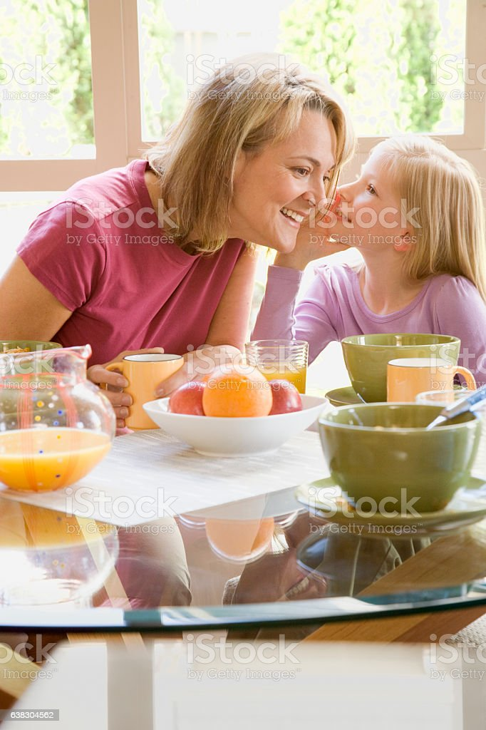 Daughter telling mother a secret during breakfast at home stock photo