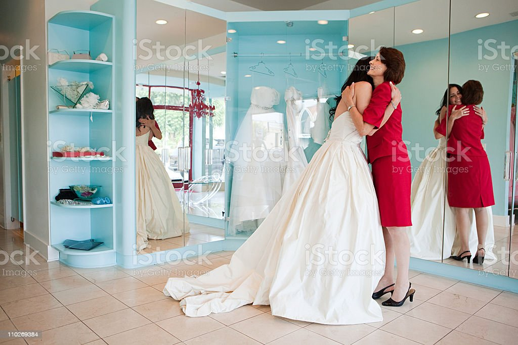 Daughter trying on wedding dress, embracing mother stock photo
