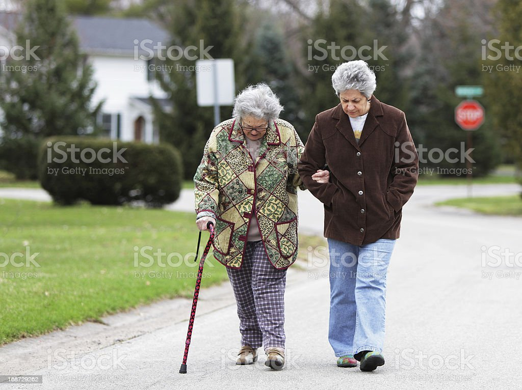 Daughter Walking with Mother Using Cane royalty-free stock photo