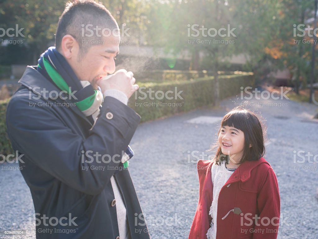 Daughter watching father drinking hot tea in the morning stock photo
