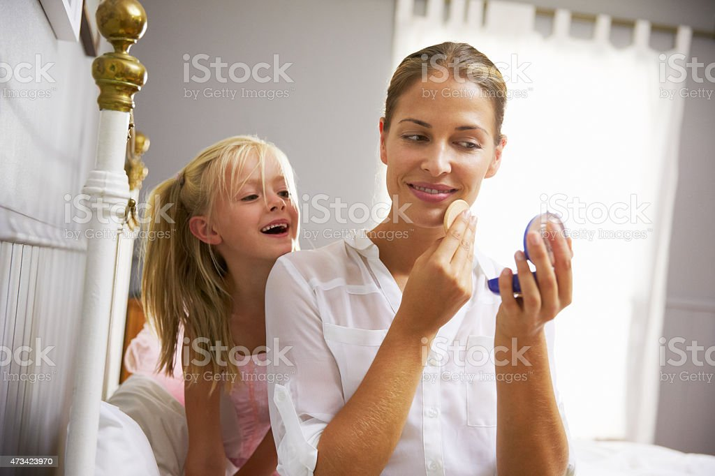 Daughter Watching Working Mother Put On Make Up stock photo
