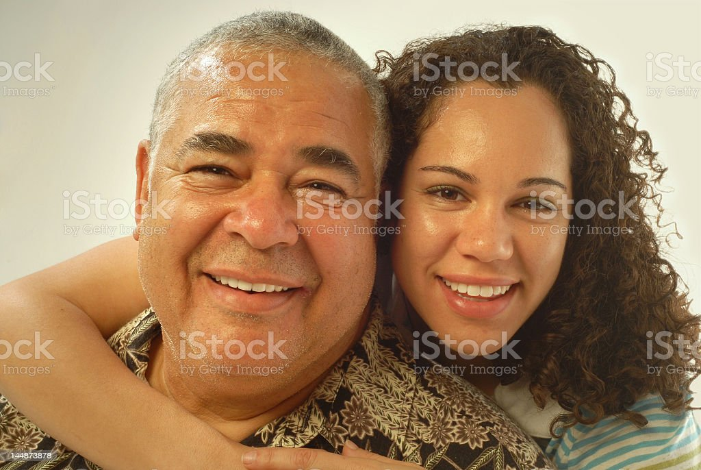 Daughter with her arm around her father both smiling stock photo