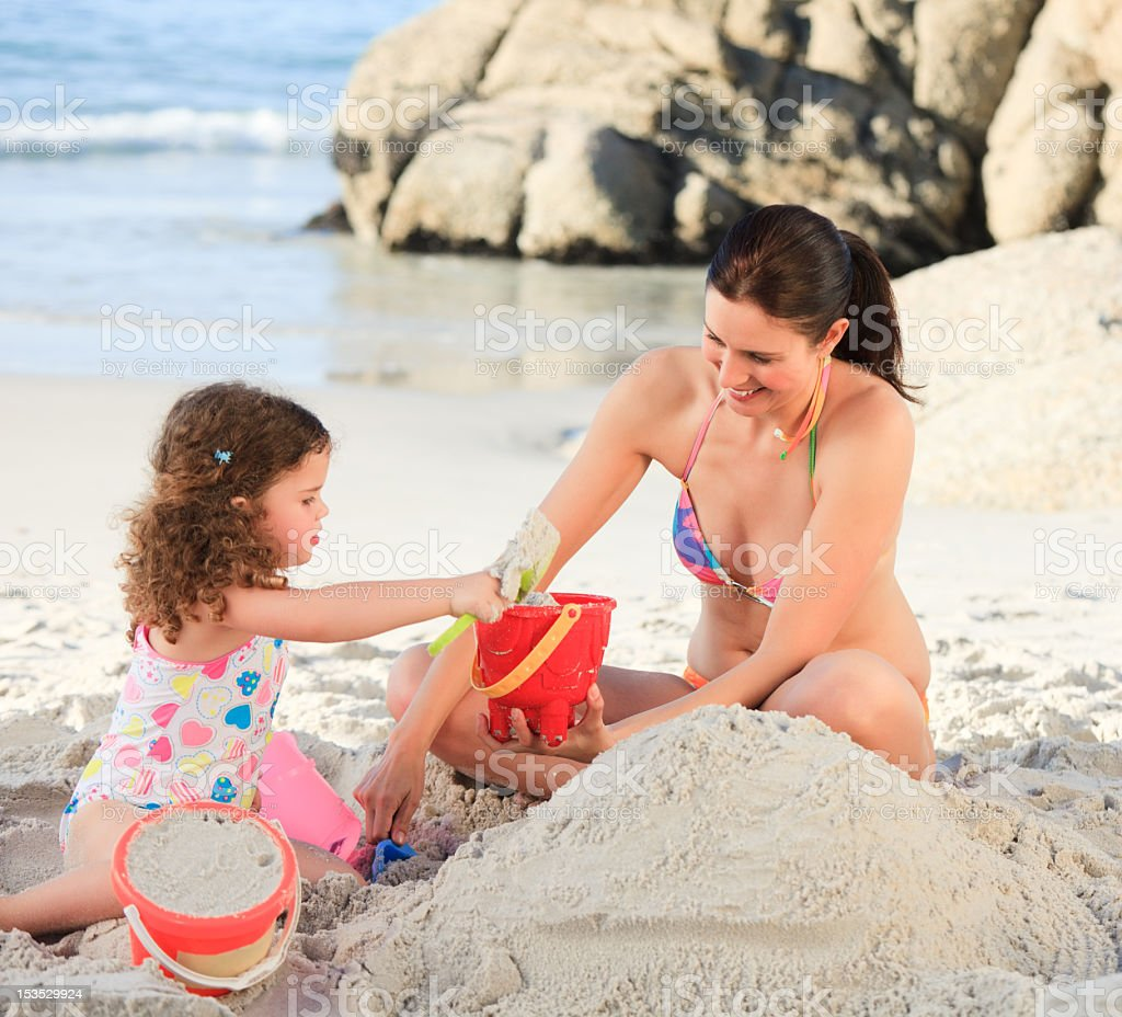 Daughter with her mother making a sand castle royalty-free stock photo