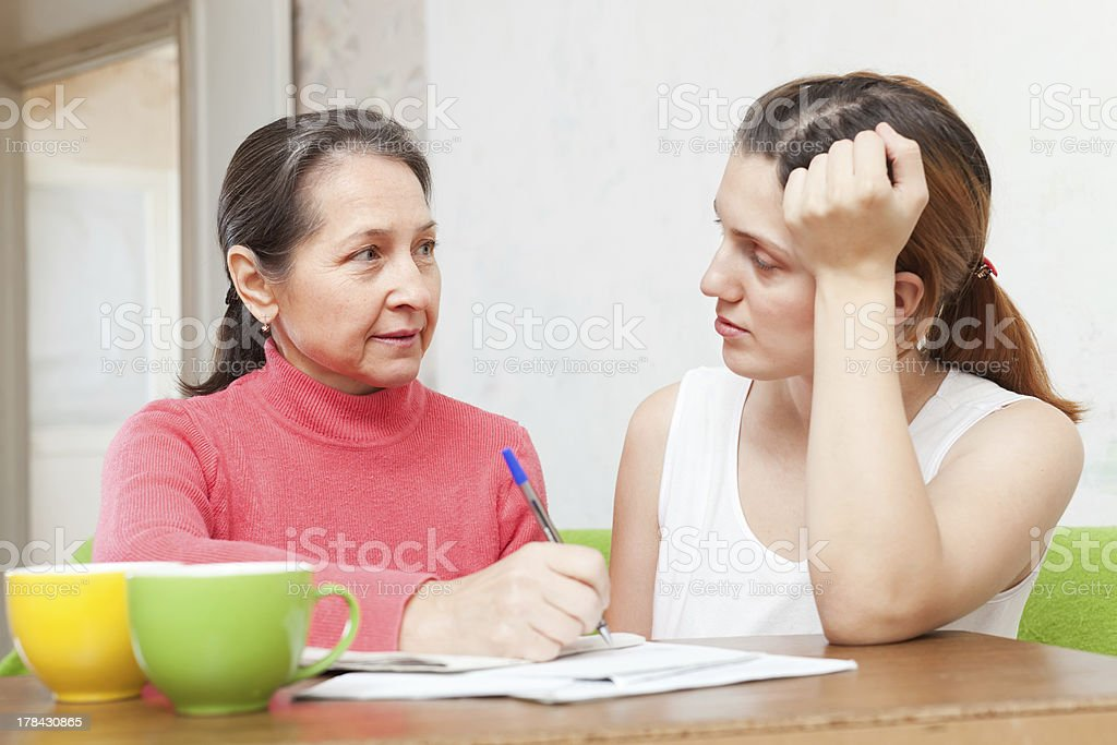 daughter with mature mother  fills in the documents royalty-free stock photo