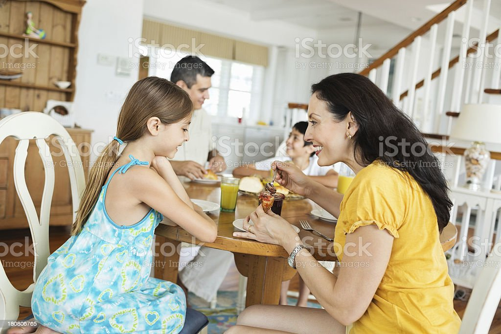 Daughter With Mother Applying Jam On Croissant royalty-free stock photo