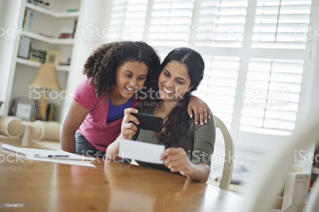 Daughter With Mother Depositing Bank Slip Through Mobile Phone royalty-free stock photo