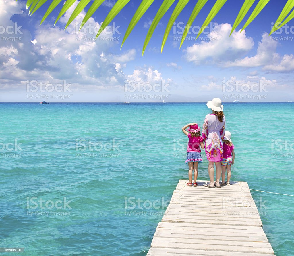 Daughters and mother in jetty on tropical beach royalty-free stock photo